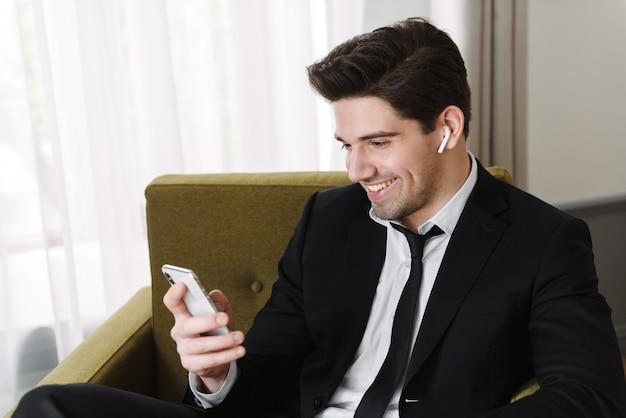Confiant bel homme vêtu d'un costume assis dans un fauteuil à l'intérieur, portant des écouteurs sans fil, tenant un téléphone mobile