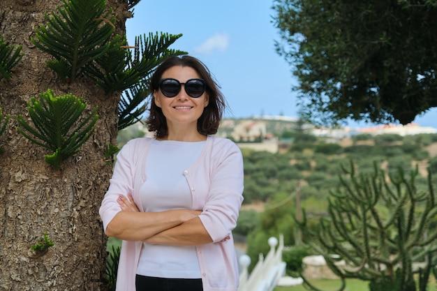 Confiant belle femme d'affaires mature propriétaire d'entreprise touristique, hôtel posant les bras croisés. paysage de fond de villégiature, plantes tropicales, espace copie