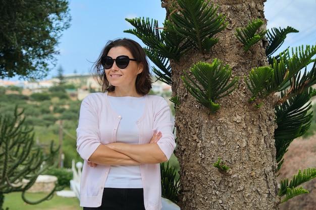 Confiant belle femme d'affaires mature propriétaire d'entreprise touristique, hôtel posant les bras croisés