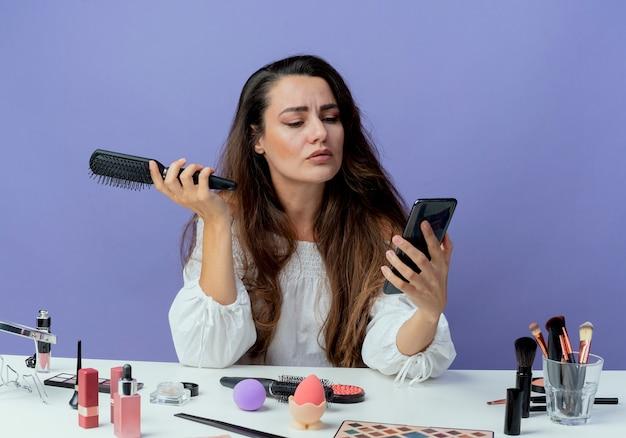 Confiant belle fille est assise à table avec des outils de maquillage détient un peigne à cheveux regardant téléphone isolé sur mur violet