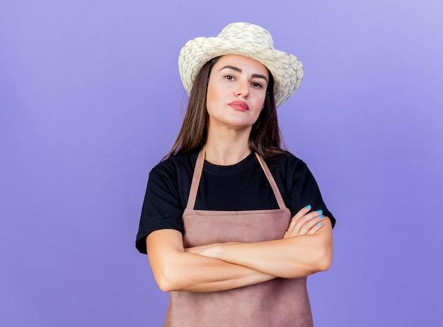 Confiant belle fille de jardinier en uniforme portant chapeau de jardinage croisant les mains isolés sur fond bleu