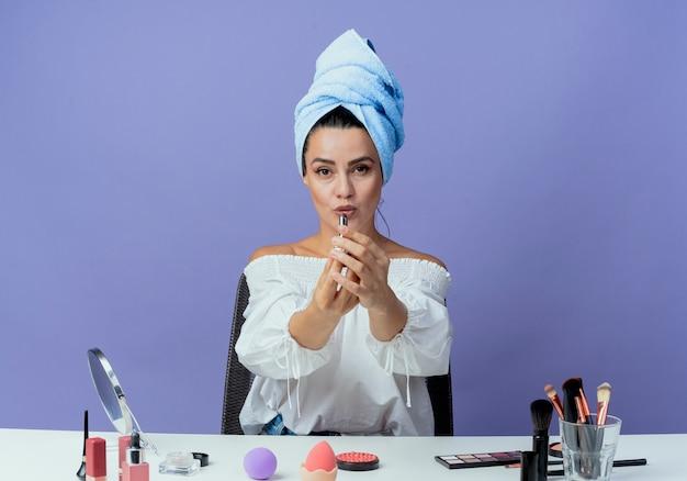 Confiant belle fille serviette de cheveux enveloppé se trouve à table avec des outils de maquillage tenant rouge à lèvres à isolé sur mur violet
