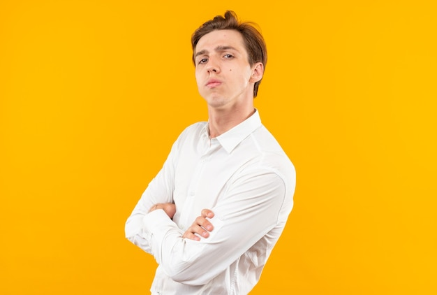 Confiant à la caméra jeune beau mec vêtu d'une chemise blanche croisant les mains