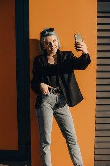 Confiant dame caucasienne aux cheveux bleus faisant un selfie à l'extérieur devant le soleil