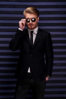 Confiant dans son beau look. beau jeune homme en tenue de soirée ajustant ses lunettes de soleil et tenant une main dans les poches en se tenant debout sur fond rayé