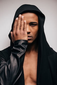 Confiant dans son style. confiant jeune homme africain en chemise à capuche