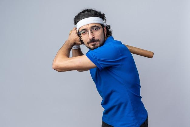 Confiant debout dans les combats posent un jeune homme sportif portant un bandeau avec un bracelet tenant une batte de baseball
