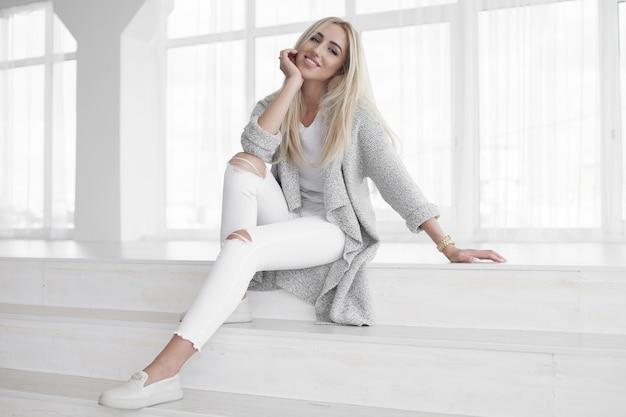 Confiant détendu jeune femme assise sur les marches en jeans blanc à la mode un sourire amical rayonnant