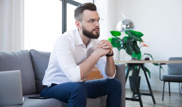 Confiant élégant bel homme d'affaires barbu dans des verres et des vêtements intelligents formels est assis sur le canapé dans le bureau ou la chambre moderne