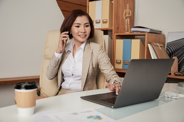 Confiant, ethnique, femme affaires, parler téléphone, dans, bureau