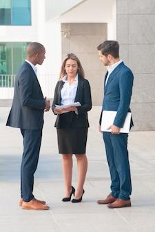 Confiant, femme affaires, conversation, à, collègues masculins, dehors