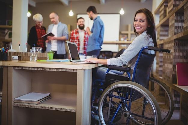 Confiant femme d'affaires handicapée utilisant un ordinateur portable au bureau