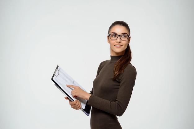 Confiant, femme affaires, sourire, tenir presse-papiers