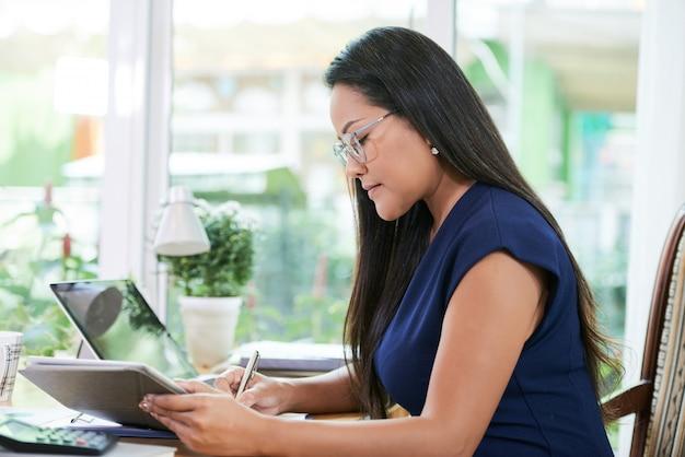 Confiant femme d'affaires travaillant avec tablette au bureau
