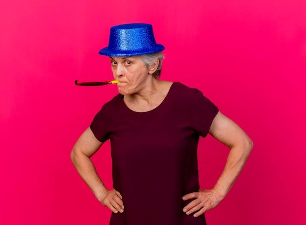 Confiant femme âgée portant chapeau de fête met les mains sur la taille soufflant sifflet sur rose