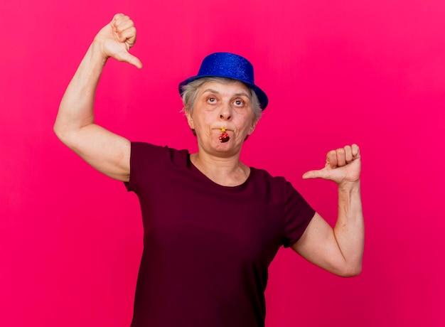 Confiant femme âgée portant chapeau de fête se pointe à elle-même avec deux mains soufflant sifflet sur rose