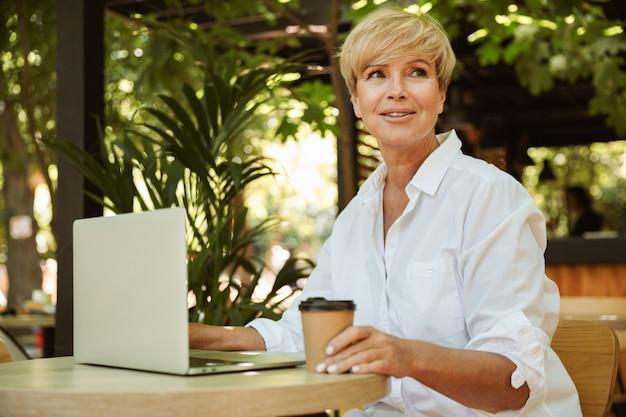 Confiant femme mature assise dans un café
