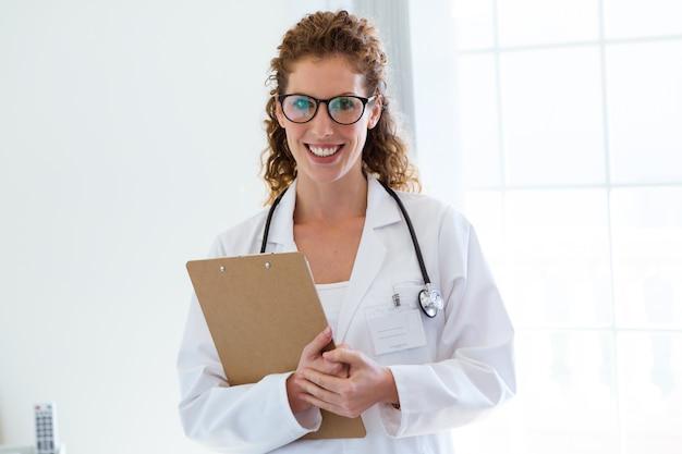 Confiant femme médecin au bureau en regardant la caméra.