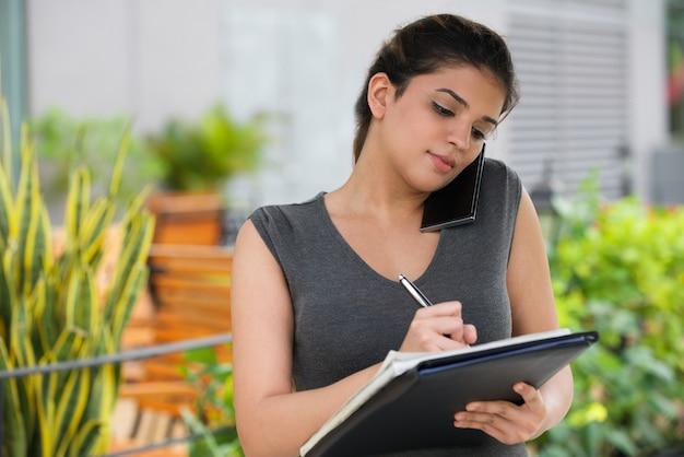 Confiant, femme, secrétaire, conversation, mobile, téléphone