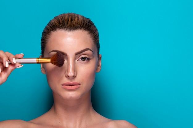 Confiant, femme, tenue, pinceau maquillage