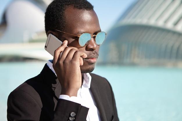Confiant homme d'affaires afro-américain portant un costume formel noir et des lunettes rondes en miroir vérifiant la messagerie vocale sur le chemin du retour au bureau après le déjeuner