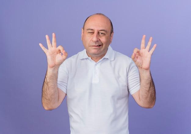 Confiant homme d'affaires mature occasionnel clignant des yeux et faisant des signes ok isolés sur fond violet
