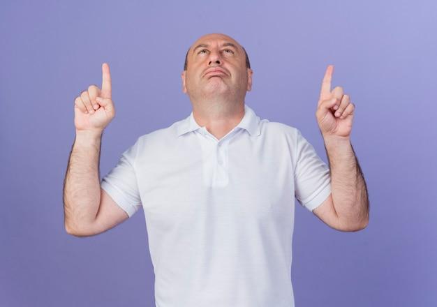 Confiant homme d'affaires mature occasionnel à la recherche et pointant vers le haut isolé sur fond violet