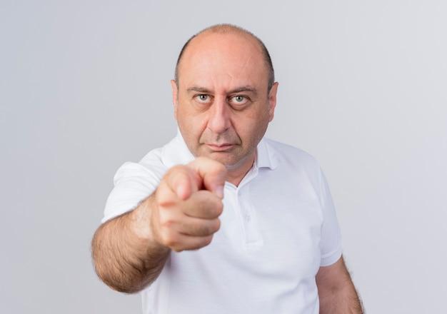 Confiant homme d'affaires mature occasionnel regardant et pointant vers la caméra isolée sur fond blanc