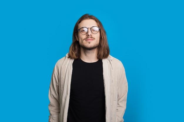 Confiant l'homme aux cheveux longs avec barbe regarde la caméra portant des lunettes et une chemise sur un mur de studio bleu