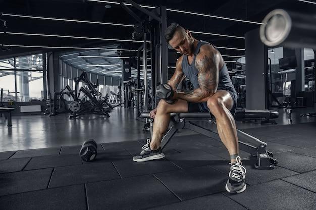 Confiant. jeune athlète caucasien musclé pratiquant dans la salle de gym avec les poids. modèle masculin faisant des exercices de force, entraînant le haut du corps. bien-être, mode de vie sain, concept de musculation.