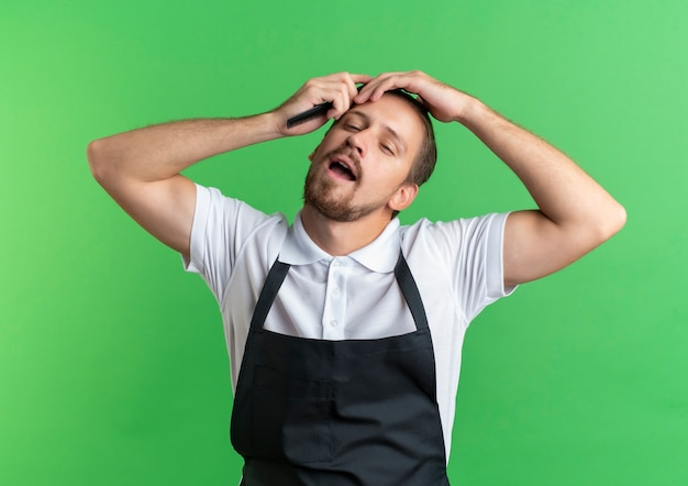 Confiant jeune beau coiffeur en uniforme se peignant les cheveux et mettant la main sur la tête isolé sur vert