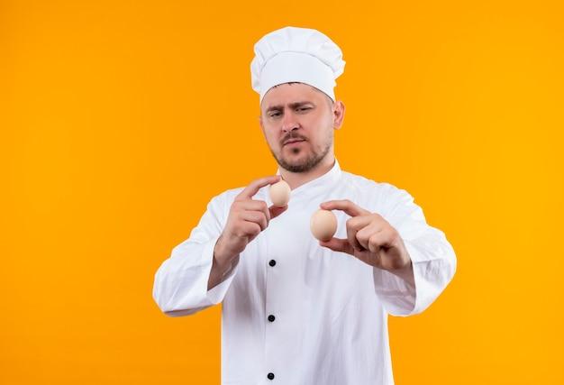 Confiant jeune beau cuisinier en uniforme de chef tenant et regardant des œufs isolés sur un mur orange