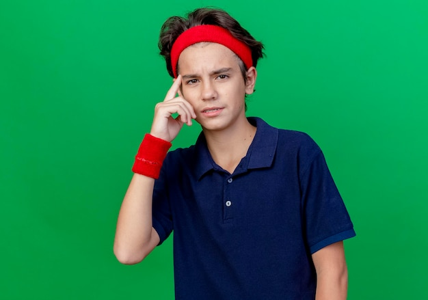 Confiant jeune beau garçon sportif portant un bandeau et des bracelets avec un appareil dentaire à l'avant faisant penser geste isolé sur mur vert avec espace copie
