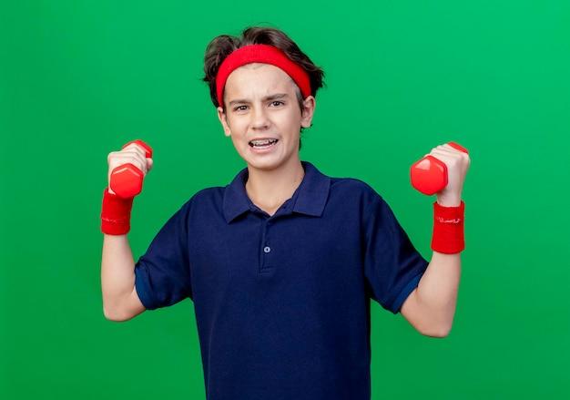 Confiant jeune beau garçon sportif portant un bandeau et des bracelets avec un appareil dentaire tenant des haltères à l'avant isolé sur un mur vert