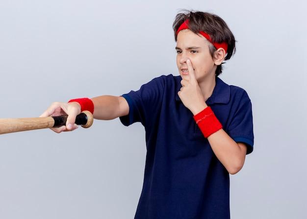 Confiant jeune beau garçon sportif portant un bandeau et des bracelets avec des appareils dentaires à côté en mettant le doigt sur le nez qui s'étend sur une batte de baseball isolé sur un mur blanc