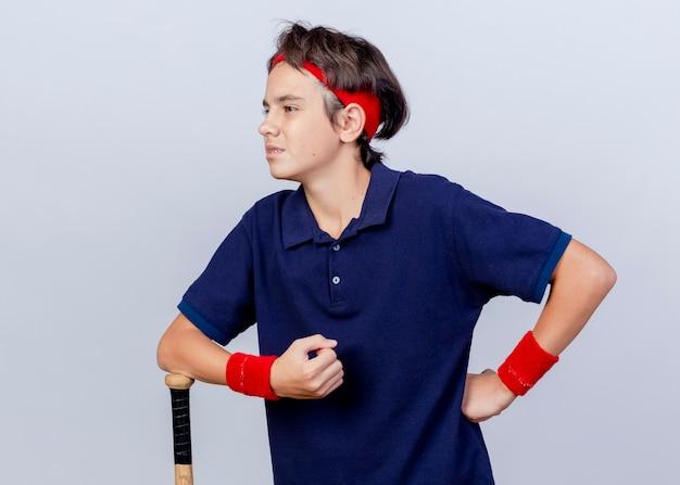 Confiant jeune beau garçon sportif portant un bandeau et des bracelets avec des appareils dentaires en gardant la main sur la taille en mettant le bras sur une batte de baseball à côté isolé sur un mur blanc avec espace de copie
