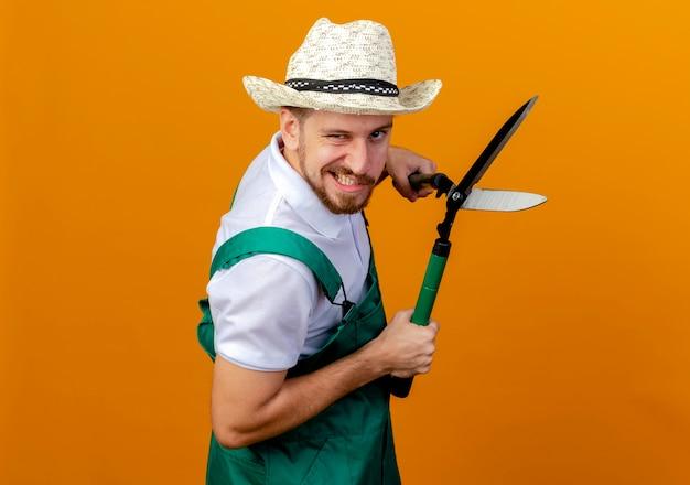 Confiant jeune beau jardinier slave en uniforme et chapeau debout en vue de profil tenant des sécateurs à isolé