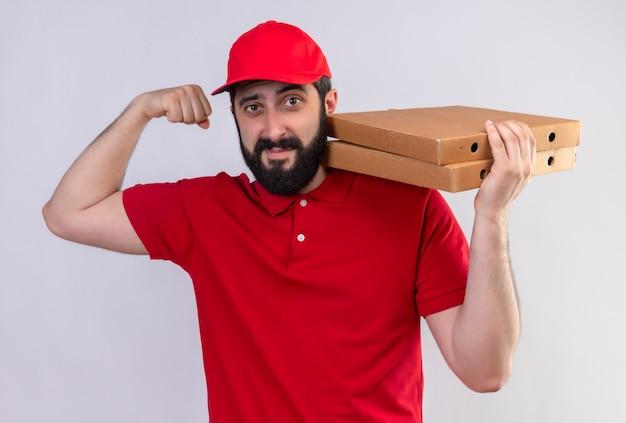 Confiant jeune beau livreur caucasien vêtu d'un uniforme rouge et une casquette tenant des boîtes de pizza sur l'épaule et faisant des gestes fort isolé sur blanc