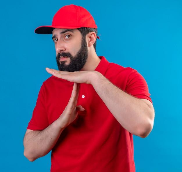 Confiant jeune beau livreur de race blanche portant l'uniforme rouge et une casquette faisant le geste de délai d'attente isolé sur bleu