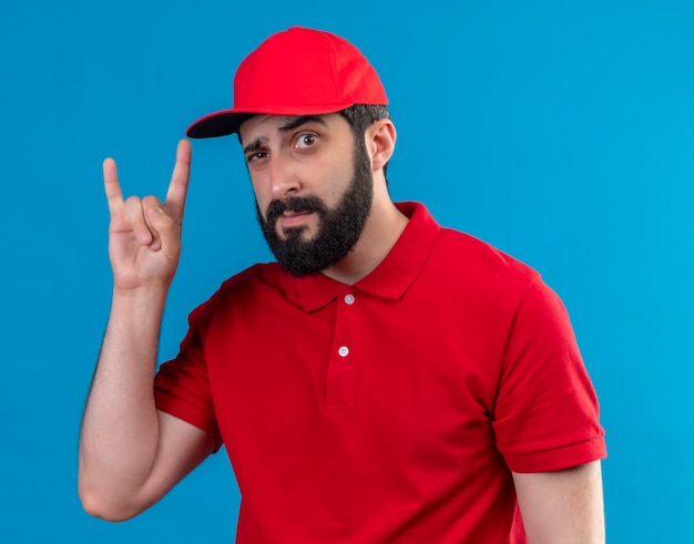 Confiant jeune beau livreur de race blanche portant l'uniforme rouge et une casquette faisant signe de roche isolé sur bleu