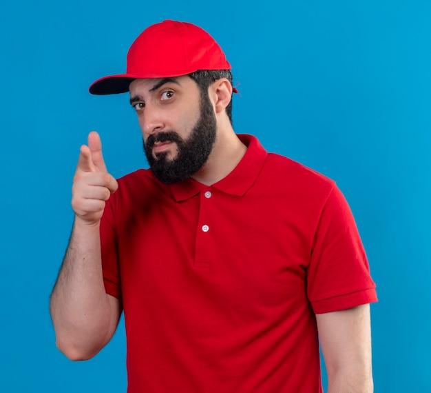 Confiant jeune beau livreur de race blanche portant l'uniforme rouge et une casquette à la recherche et pointant isolé sur bleu