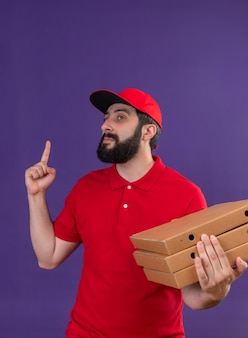 Confiant jeune beau livreur de race blanche portant l'uniforme rouge et une casquette tenant des boîtes de pizza à côté et pointant vers le haut isolé sur violet