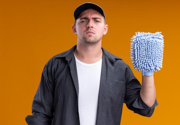 Confiant jeune beau mec de nettoyage portant un t-shirt et une casquette tenant un chiffon de nettoyage isolé sur un mur orange