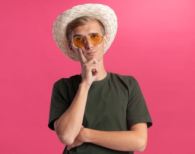 Confiant jeune beau mec portant une chemise verte et des lunettes avec un chapeau mettant le doigt sur la joue isolé sur un mur rose