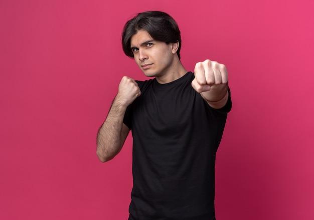 Confiant jeune beau mec portant un t-shirt noir debout dans la pose de combat isolé sur un mur rose avec espace de copie
