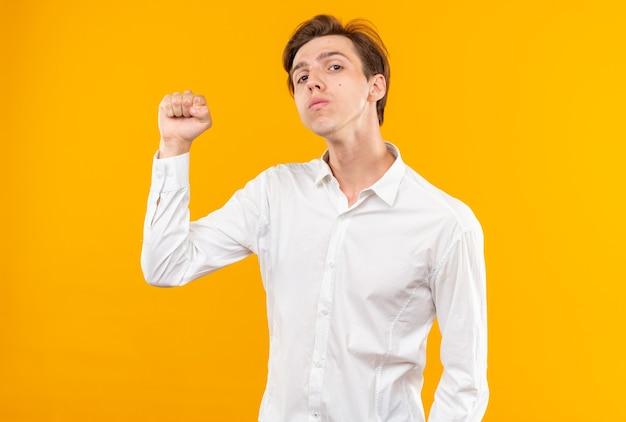 Confiant jeune beau mec vêtu d'une chemise blanche faisant un geste fort isolé sur un mur orange