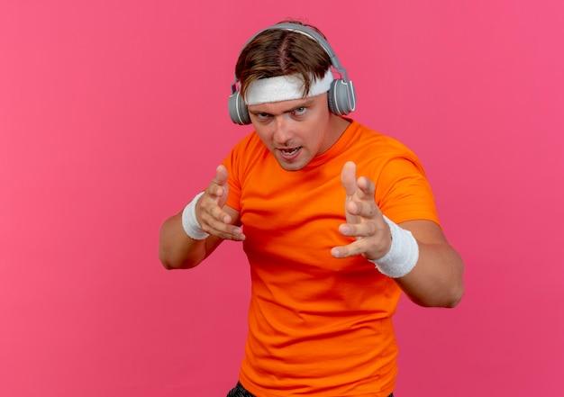Confiant jeune bel homme sportif portant un bandeau et des bracelets et des écouteurs étirant les mains isolés sur rose avec espace de copie