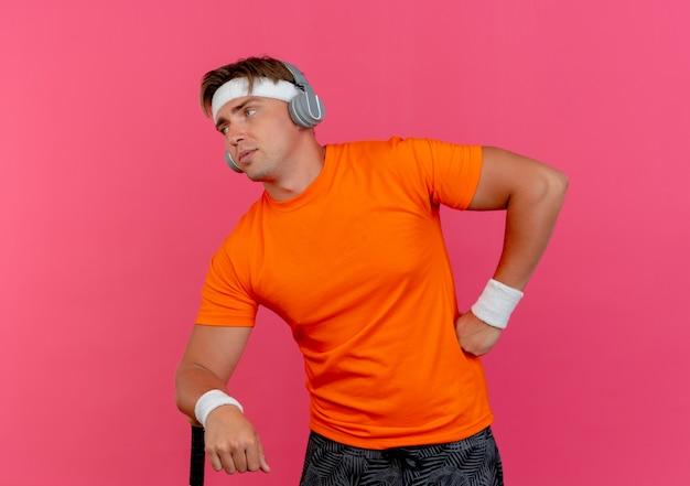 Confiant jeune bel homme sportif portant un bandeau et des bracelets et des écouteurs mettant la main sur la taille et un autre sur une batte de baseball à côté isolé sur rose avec espace de copie