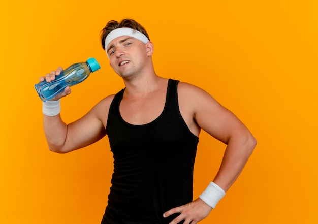 Confiant jeune bel homme sportif portant bandeau et bracelets tenant une bouteille d'eau avec la main sur la taille isolé sur orange
