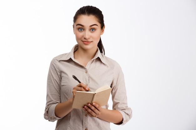 Confiant jeune belle femme d'affaires écrit dans le cahier souriant sur mur blanc